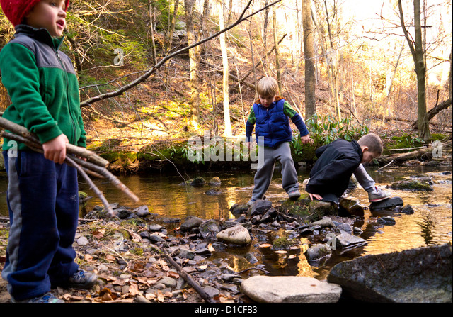 Three little boys playing in and around a stream on a fall day - Stock-Bilder