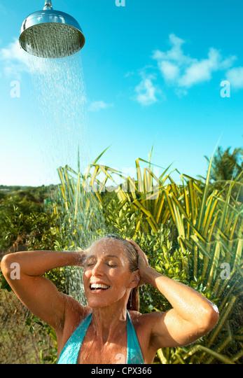 Woman enjoying cool shower outdoors - Stock-Bilder