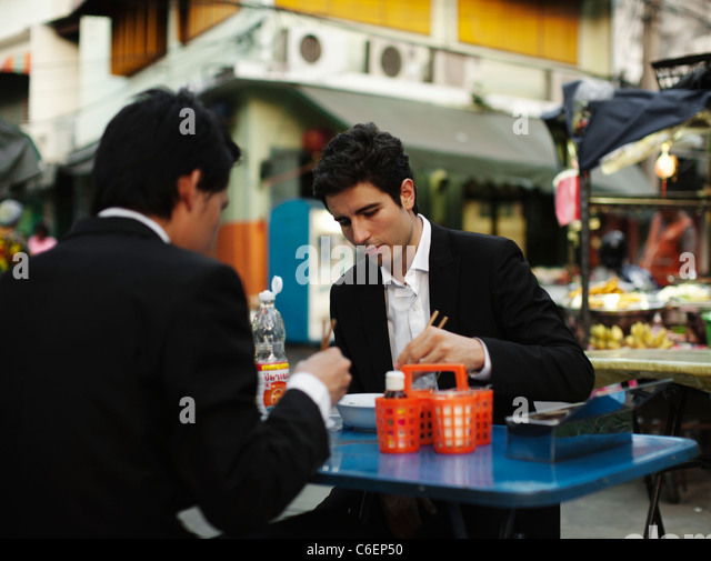 Businessmen eating lunch together outdoors - Stock Image
