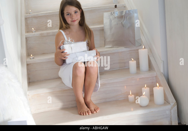 Little girl holding a Christmas present, indoors - Stock Image