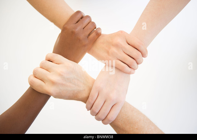 Four hands holding wrists of other people - Stock Image