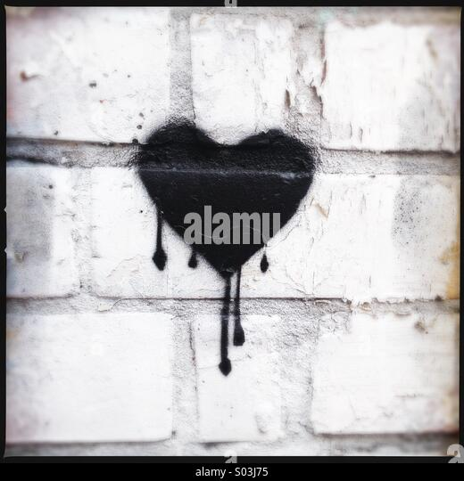 Bleeding black heart stencil graffiti. - Stock Image