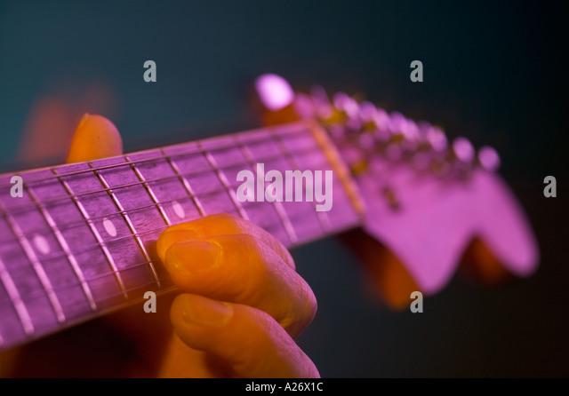 Mans fingers plucking strings on a Fender electric guitar - Stock-Bilder