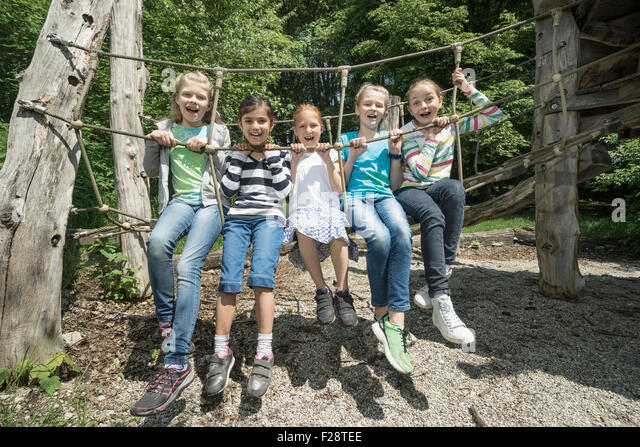 Girls sitting on rope bridge in playground, Munich, Bavaria, Germany - Stock Image