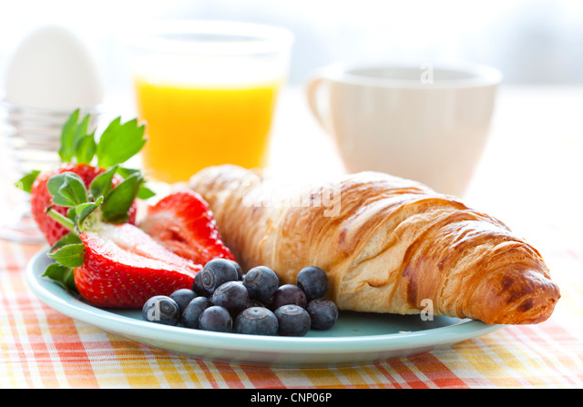 Croissant, fresh strawberries and blueberries, coffee, orange juice and an egg for healthy breakfast - Stock Image