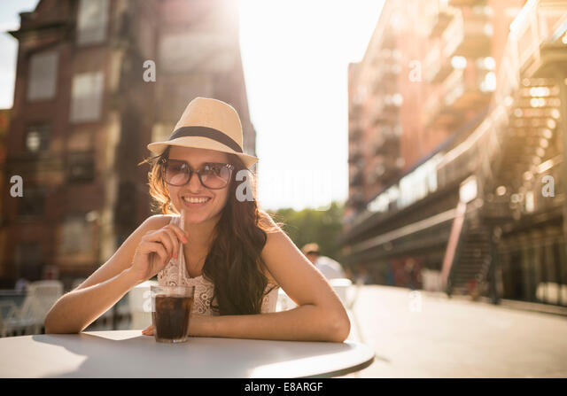 Young woman wearing hat and sunglasses with drink - Stock Image
