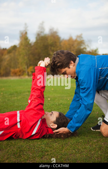 Personal trainer assisting young woman with warm up exercises - Stock Image