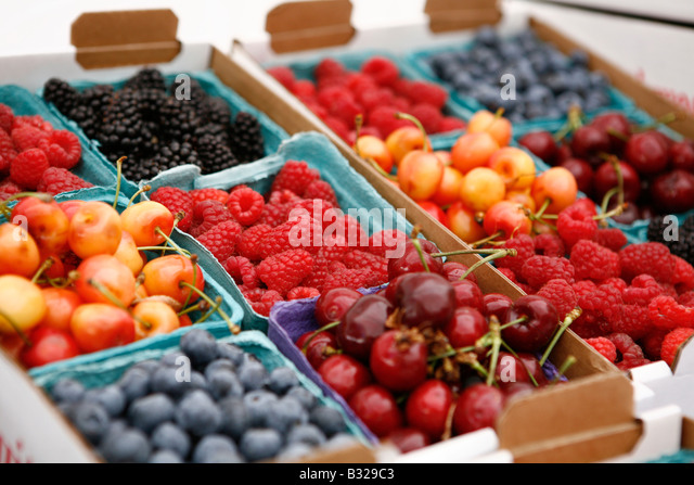 Crate of berries and cherries on display at market - Stock Image
