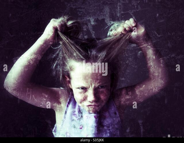 She pulls her hair in frustration and anger. - Stock Image