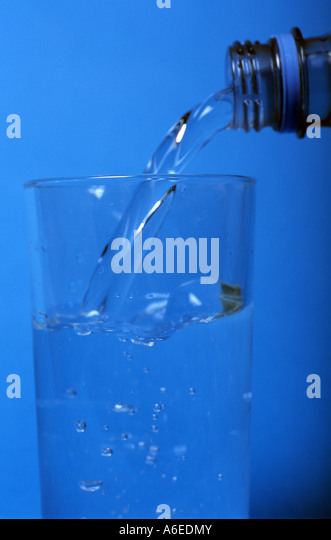 Bottled drinking water being poured into a glass. - Stock Image