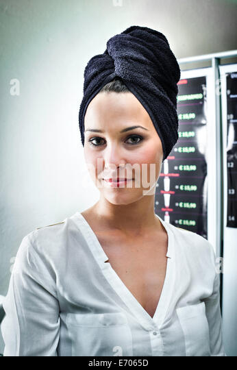 Portrait of young woman in hair salon with towel wrapped around her head - Stock-Bilder