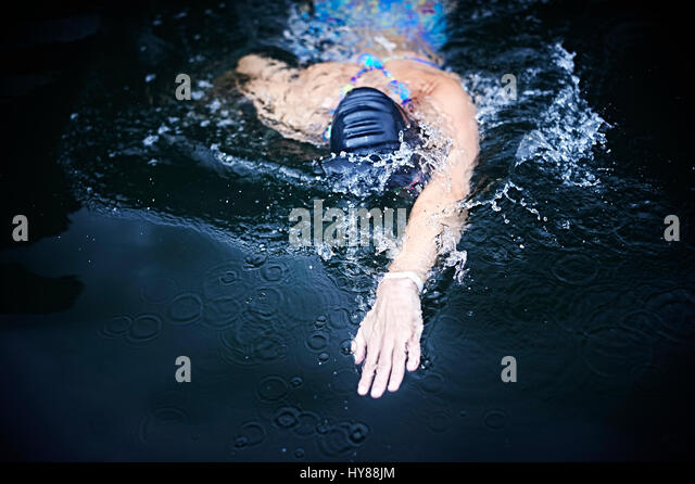 Happy confident young female swimmer in an outside pool in southern Iceland - Stock Image