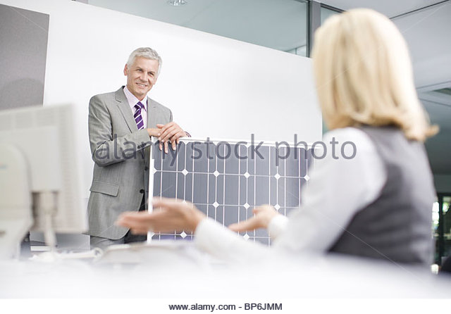 Two business colleagues discussing solar panel technology - Stock Image