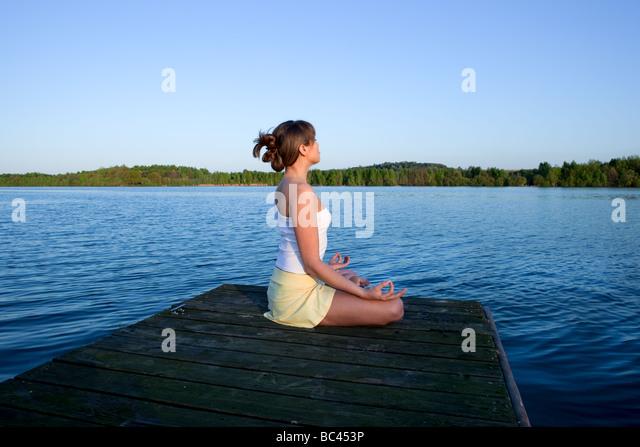 Beautiful young woman doing yoga exercise outdoors - Stock Image