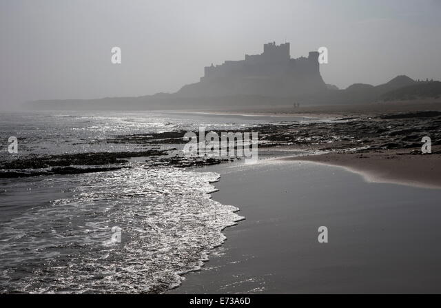 Waves breaking at Bamburgh Beach looking towards Bamburgh Castle on a misty morning, Northumberland, England, United - Stock Image