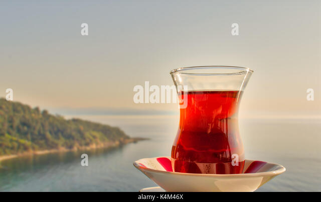 Glass of traditional Turkish tea with background of mountains of Buyukada island, Marmara sea, Istanbul, Turkey - Stock Image
