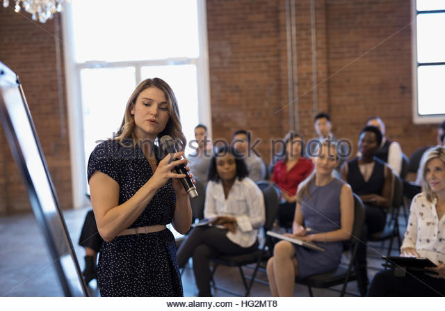 Businesswoman with microphone leading conference meeting at whiteboard - Stock Image