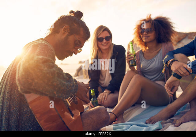 Hipster playing guitar for friends at the beach. Group of young people drinking beer and listening to music. - Stock-Bilder