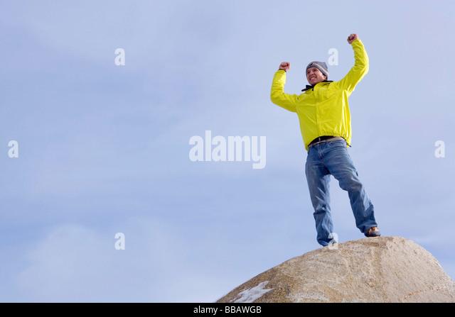 Climber celebrating on mountain peak - Stock Image
