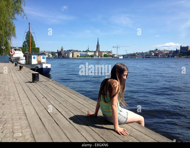 Girl sitting on wooden jetty, Stockholm, Sweden - Stock Image