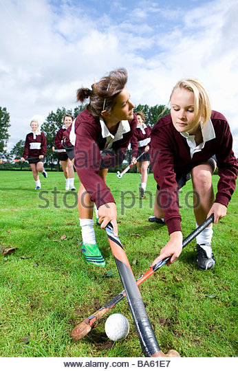 Teenage girls playing field hockey - Stock Image