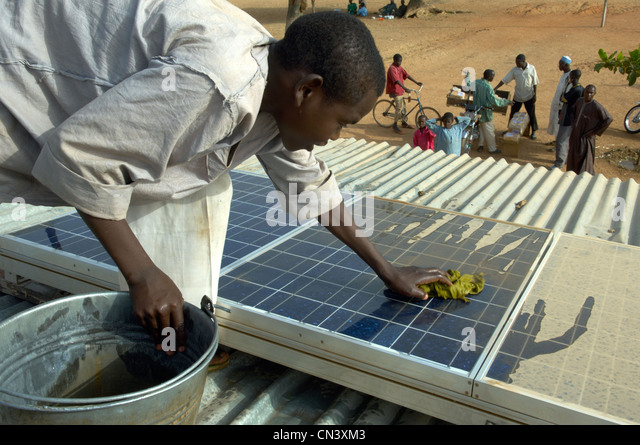 Young boy cleans dust of solar panels in Africa - Stock-Bilder