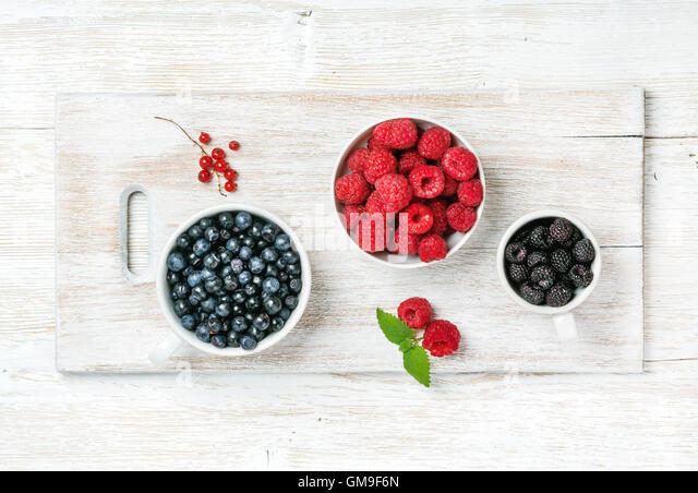 Summer garden berries in bowls on white painted wooden background - Stock Image