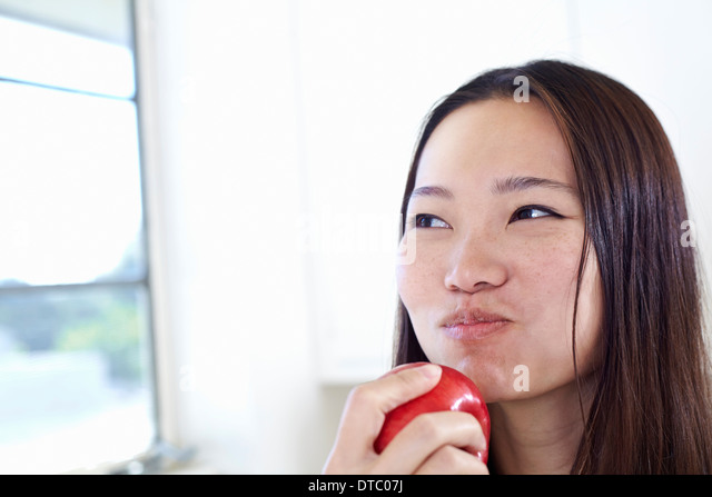 Young woman in kitchen eating red apple - Stock Image