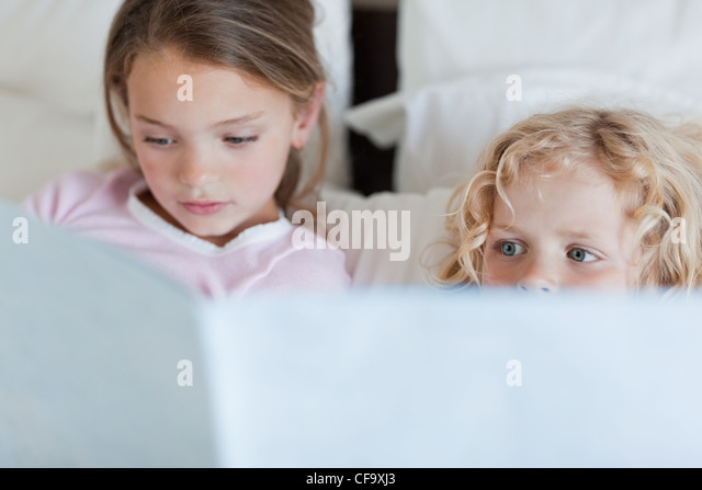 Girl reading a bed time story for her brother - Stock Image