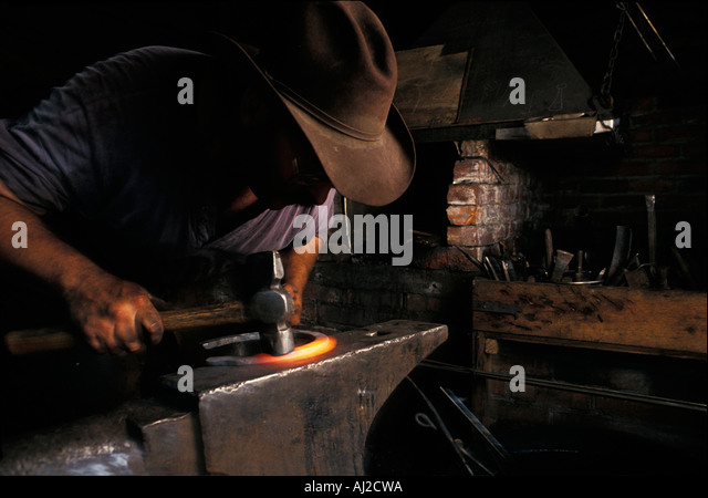 Canada British Columbia MR Michael McGuinness hammers hot steel at blacksmith s shop at Hat Creek Ranch - Stock Image