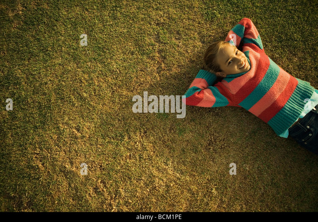 Girl lying on grass with hands behind head, high angle view - Stock Image