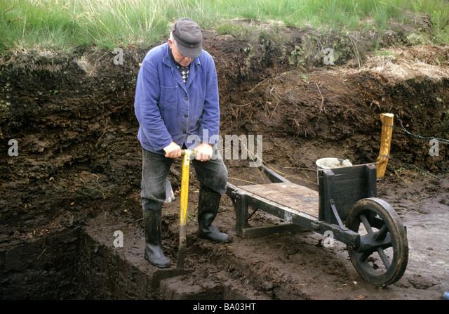 Worker cutting peat - Stock-Bilder