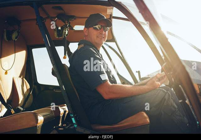 Portrait of happy male pilot sitting in the cockpit of a helicopter with a aviation map. - Stock Image