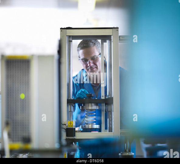 Worker using equipment to test spring - Stock Image