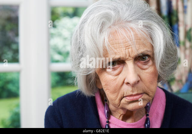 Head And Shoulders Portrait Of Angry Senior Woman At Home - Stock Image