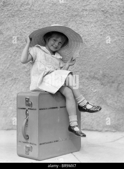 1930s PORTRAIT SMILING LITTLE GIRL SITTING ON SUITCASE WEARING BIG STRAW HAT - Stock Image