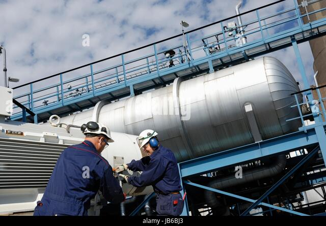 MODEL RELEASED. Industrial workers on oil and gas refinery with storage tanks. - Stock-Bilder