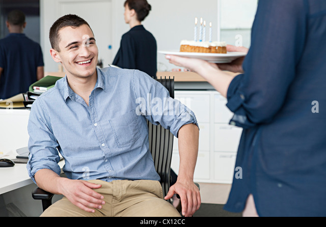 Woman bringing male colleague birthday cake in office - Stock Image