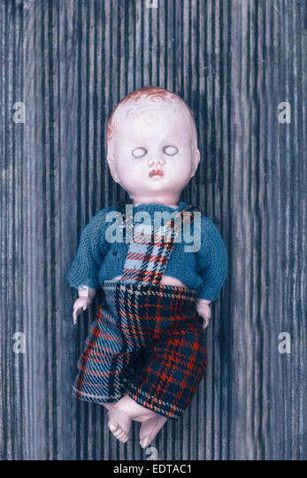 a broken doll on a wooden floor - Stock Image