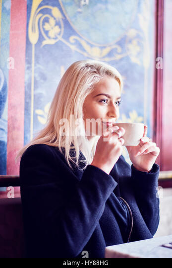 Young women drinking coffee in a cafe - Stock Image