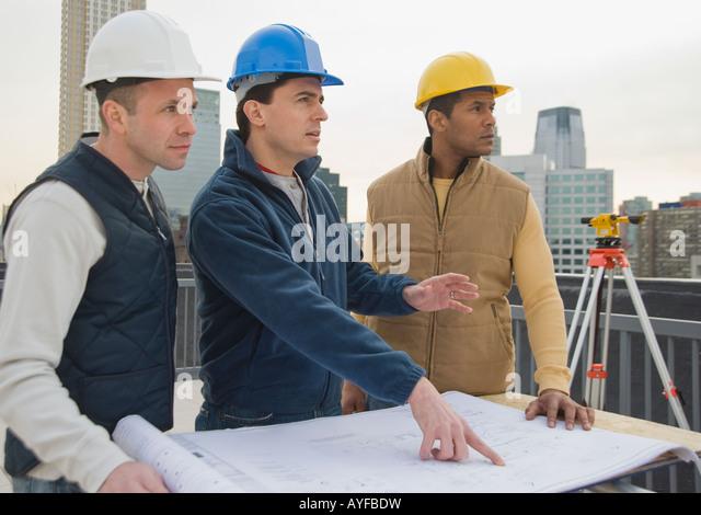 Multi-ethnic construction workers with blueprints - Stock-Bilder