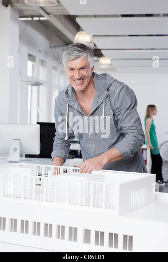 Germany, Bavaria, Munich, Man standing with architectural model in office - Stock Image