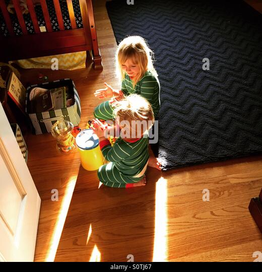 Morning playtime between brother and sister in matching pajamas - Stock Image
