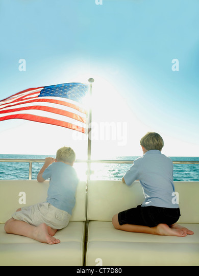 Boys in the back of a yacht with american flag, looking out to sea - Stock Image