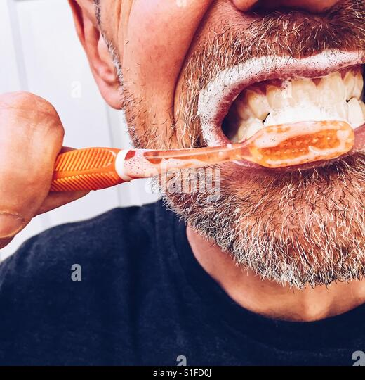 A cropped close-up of a mature man brushing his teeth - Stock-Bilder