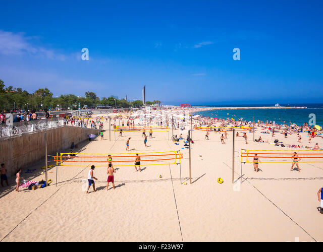 People on the crowded beach, volleyball, Port Olimpic, Barcelona, Catalonia, Spain - Stock Image