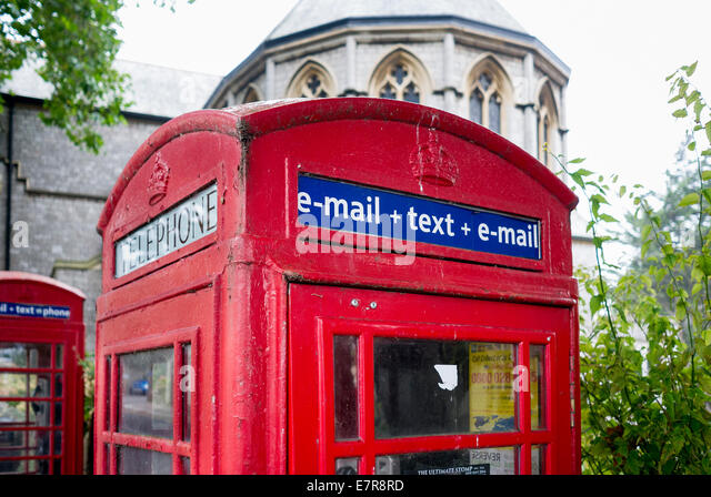 Classic red post office telephone box showing modern services including e-mail and text messaging - Stock-Bilder