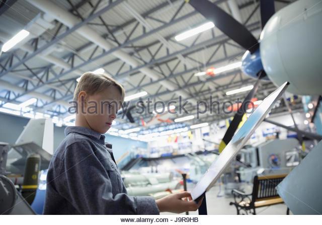 Curious boy reading information board below Air Force airplane in war museum hangar - Stock-Bilder