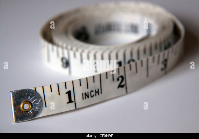 Tape measure marked in imperial feet and inches - Stock Image