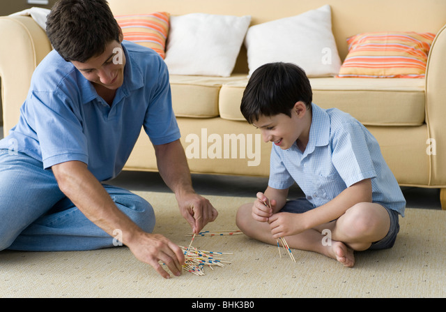 Father and son playing pick up sticks - Stock Image